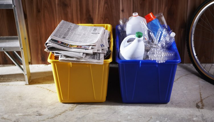 A recycling bin filled with paper sits in the garage.