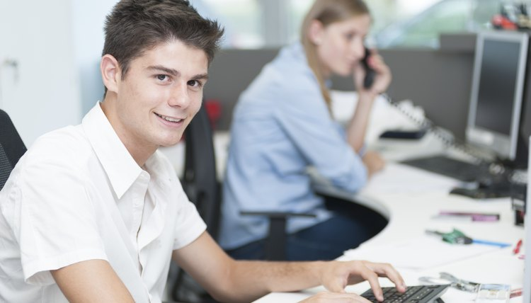 Teenager at computer office first job