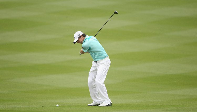 Both of McIlroy's knees are flexed and parallel to his target line as he comes down to hit the ball.