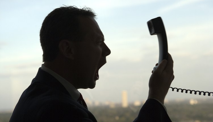 Businessman yelling at telephone receiver