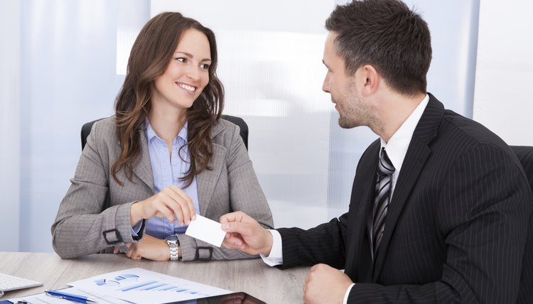 Businessman And Businesswoman Exchanging Visiting Card At Office Desk