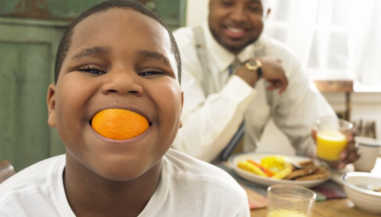 Boy with an orange in his mouth.