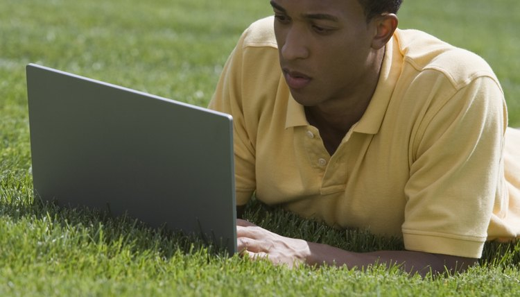 Student working on laptop on campus lawn.
