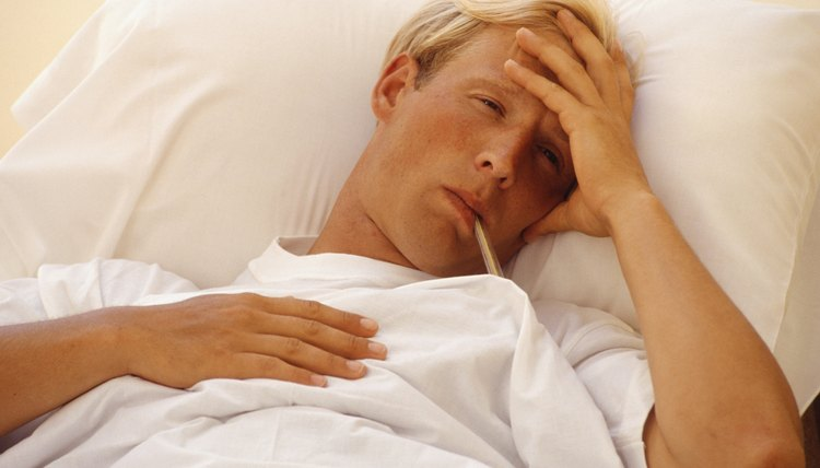 Man in bed with thermometer in mouth