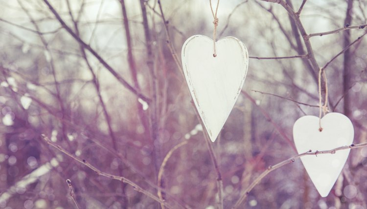 Cut hearts and snowflakes from white plastic containers to hang on trees in the yard.