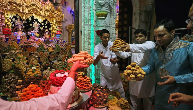Hindus make offerings to a shrine inside a mandir.