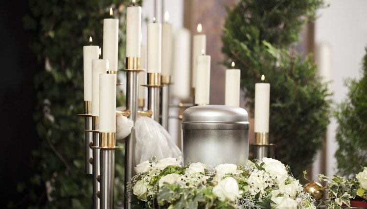 An urn displayed on a alter with candlesticks and flowers.