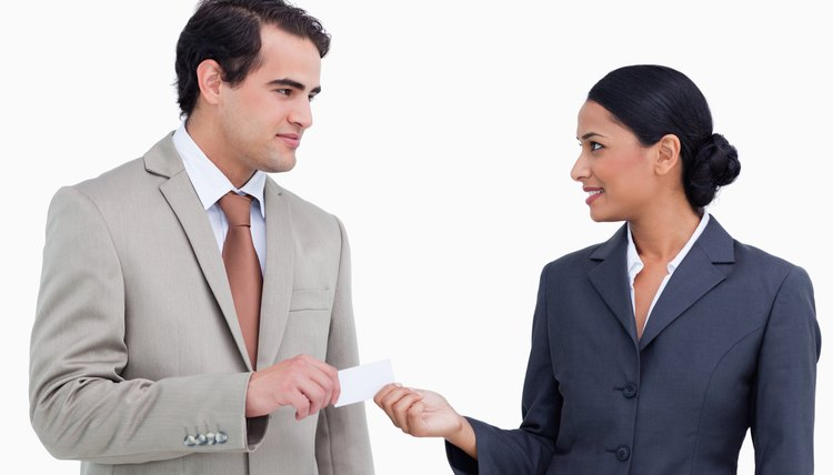 Saleswoman handing business card over to costumer