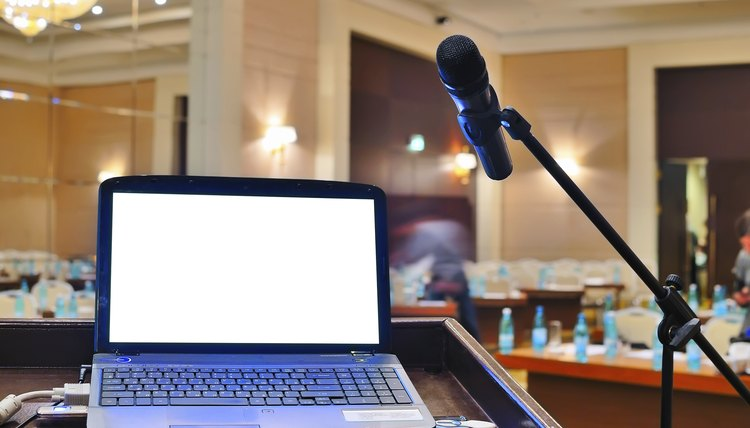A laptop on a rostrum next to a microphone in a large meeting room.