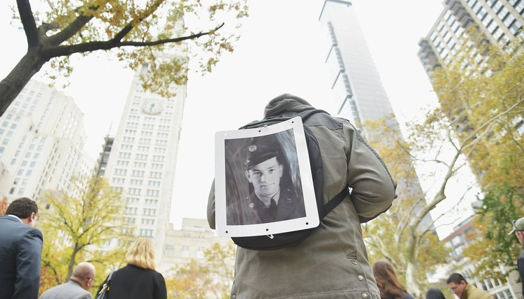 A parade attendee on Veteran's Day exhibiting a portrait of his grandfather who served in the military.
