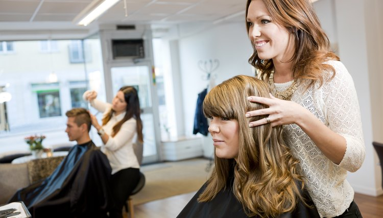 A hair stylist smiles with a client while looking at her hair in the mirror.