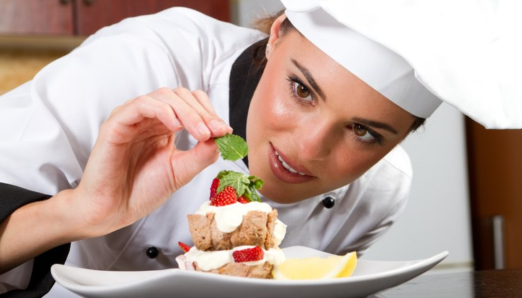 female chef decorating food in kitchen