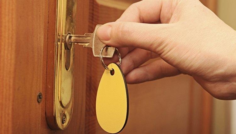 Hand, woman unlocking a door