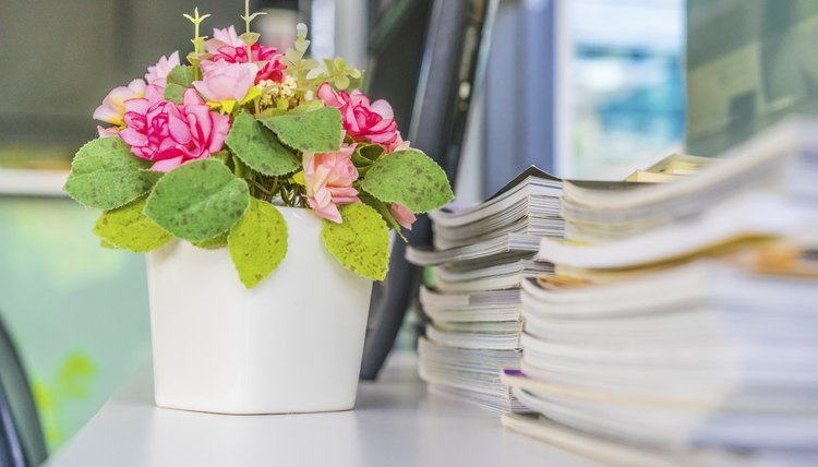 A floral arrangement sitting on a desk in the office.
