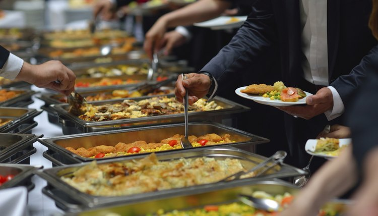 People gather around the buffet to help themselves to food