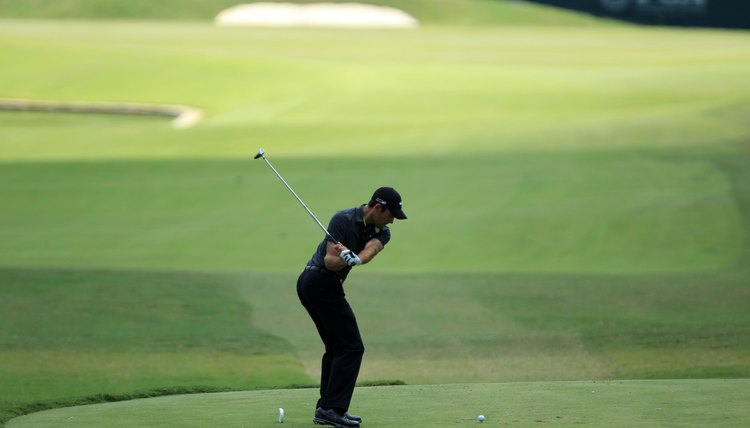 As professional player Charl Schwartzel, the 2011 Masters champion, makes his downswing, his right knee stays bent so he doesn't tilt his spine toward the target.