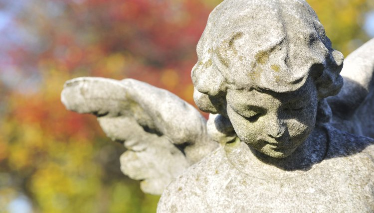 A close-up of a stone statue in a cemetary in autumn.