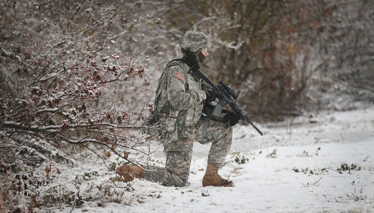 Army officer kneeling in the snow with gun.
