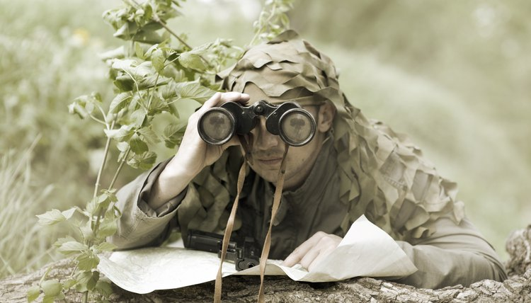 Camouflaged soldier with binoculars and map.