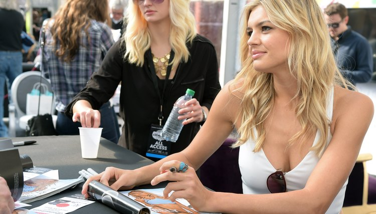 A Sports Illustrated model signing an autograph at an event.