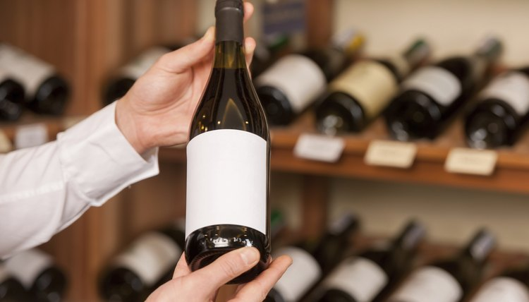 Man holding up nice bottle of wine in store