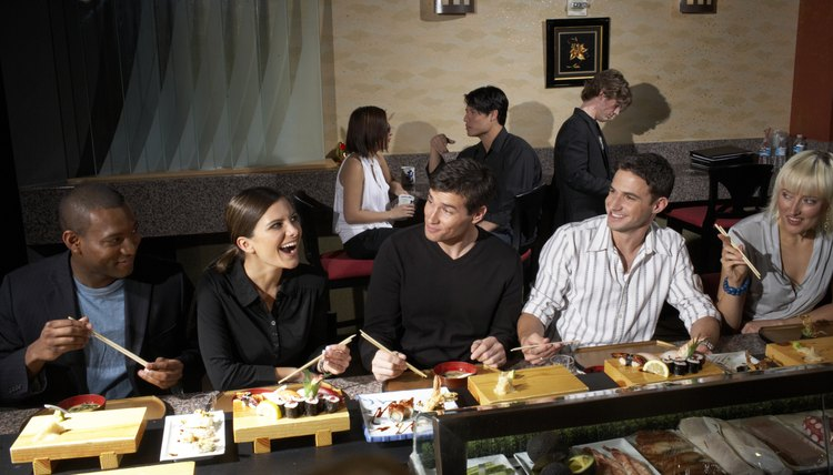 Five people sitting at counter in sushi bar, others in background, woman laughing
