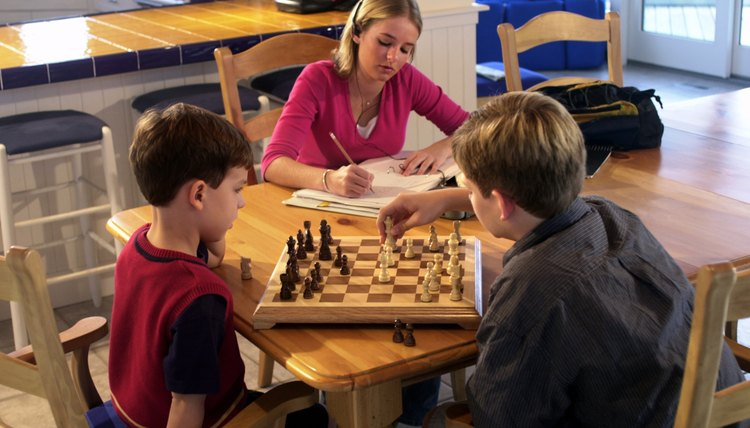 Teenage girl doing homework while brothers play chess