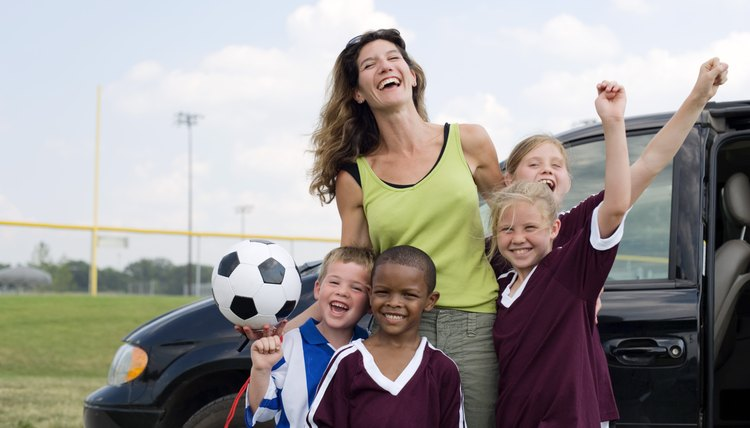 Woman and children in soccer uniforms embracing by van