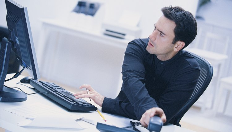 Man reaching for telephone and typing on computer