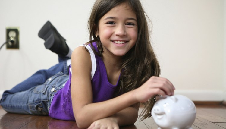 Portrait of a girl inserting coins into a piggy bank