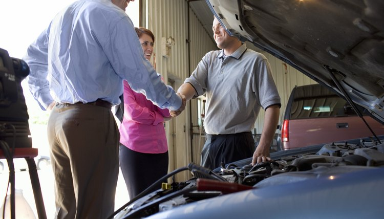 Couple shaking hands with auto mechanic