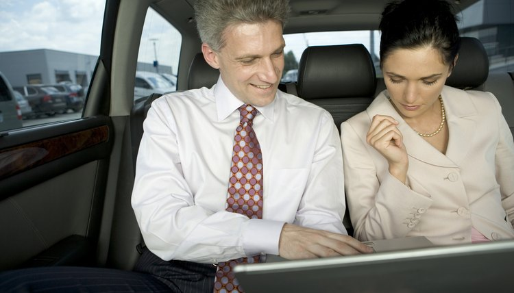 Businesspeople looking at laptop in backseat of vehicle