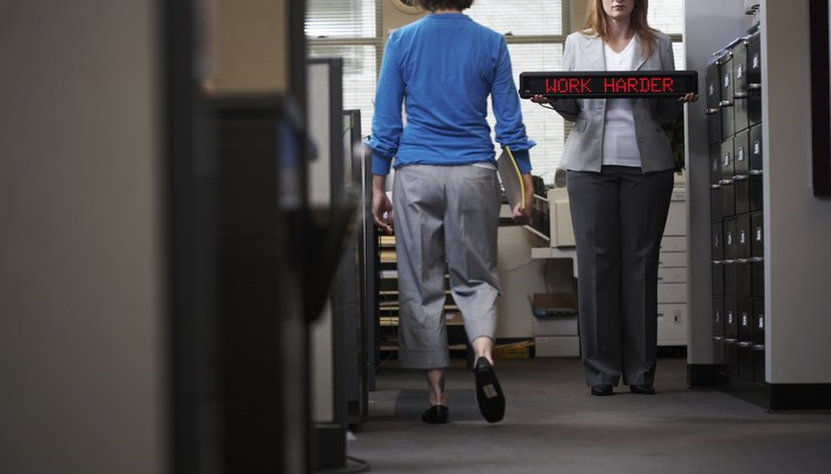 Woman walking towards another woman holding 'Work Harder' LED sign in office corridor