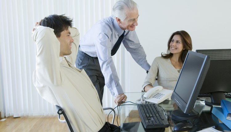 Businessman talking to businesspeople at computers