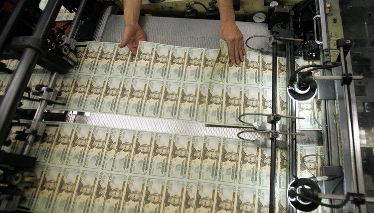 Worker looks for defective bills in newly printed U.S. twenty dollar bill sheets