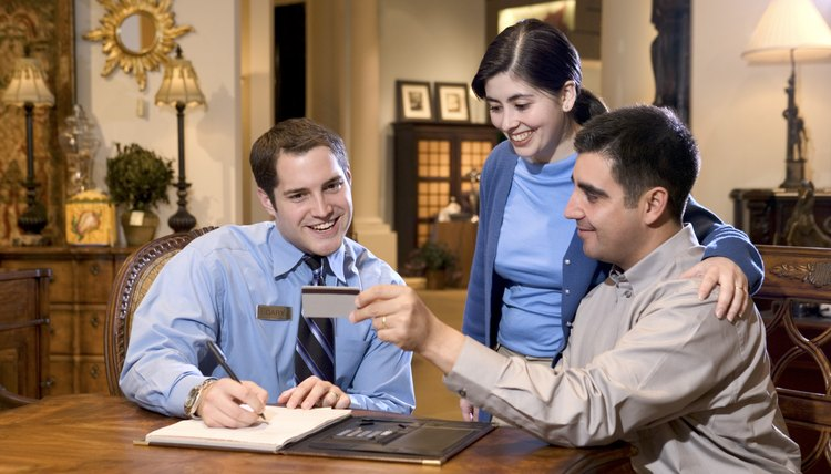 Couple giving credit card to salesman