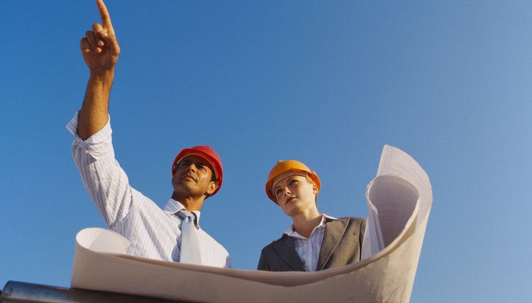 Low angle view of a young woman and a young man wearing hardhats holding design plans