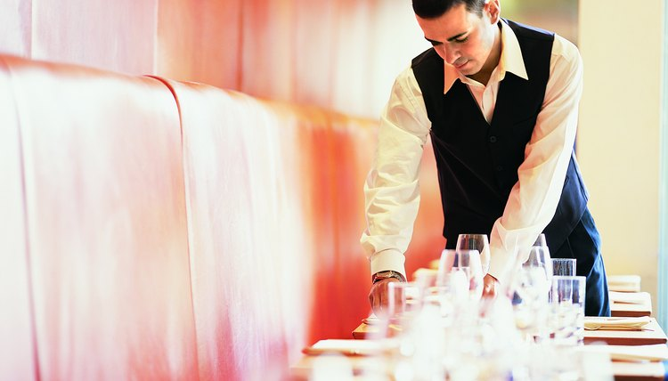 waiter clearing a table in a restaurant - Table Busser Job Description