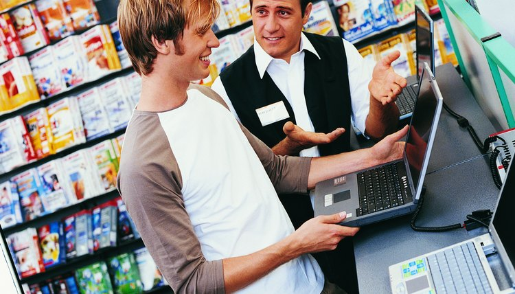 Shop Assistant Giving a Customer Advice About a Laptop in a Computer Shop