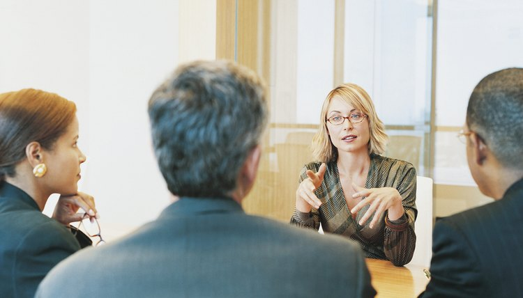 Businesswoman Sitting in an Interview Talking to a Small Group of Business People