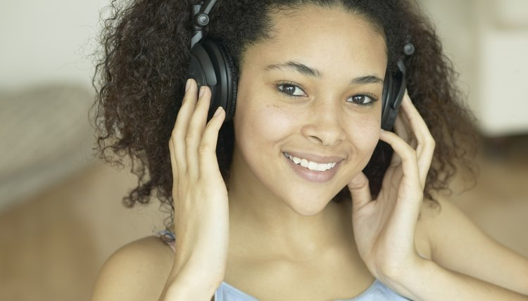 Young girl listen to music on headphones.