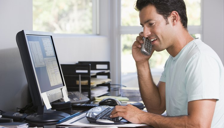 working for home office. Man In Home Office On Telephone Using Computer And Smiling Working For
