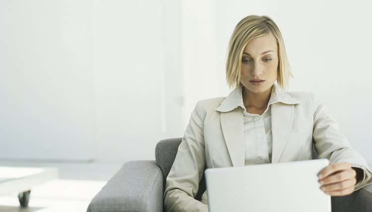 Mid adult businesswoman sitting in armchair using laptop,upper half