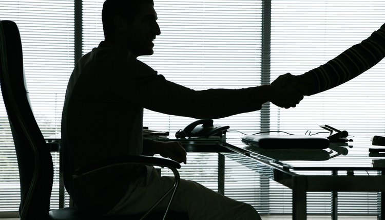 Businessman at desk shaking person's hand