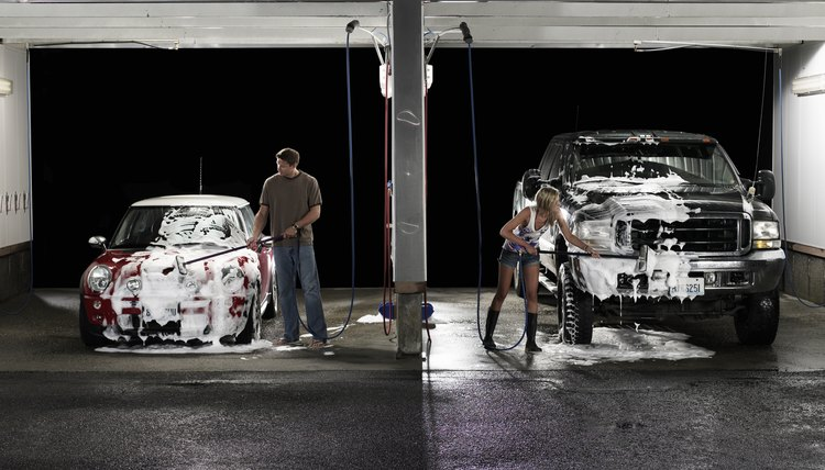 Man and woman washing cars next to each other