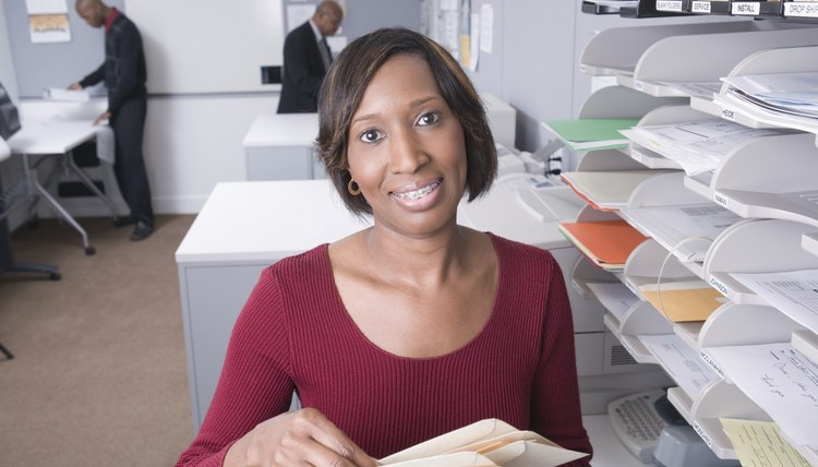 Portrait of mature female office worker holding letters, smiling, others in background