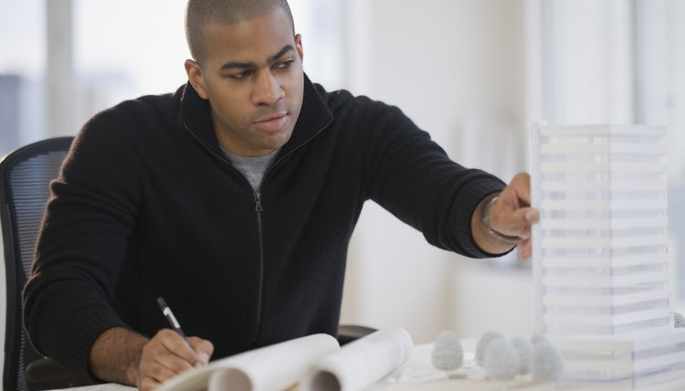 African American architect working on building model