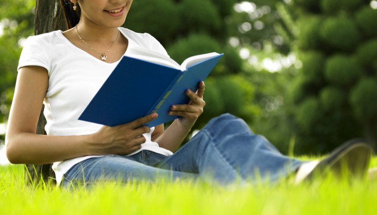 Fifth grade student reading from book in field.