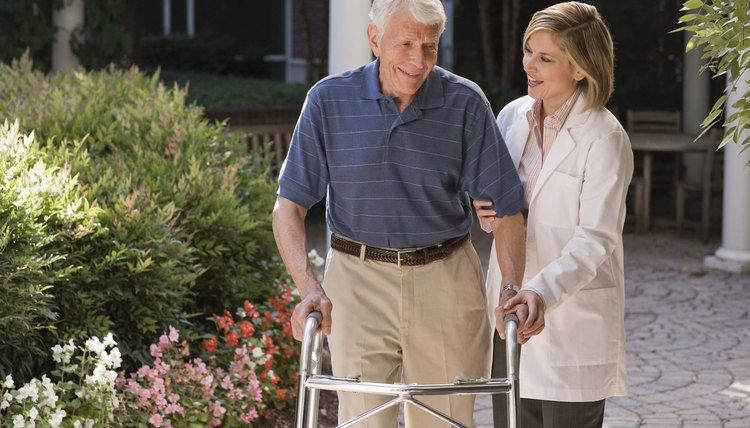Doctor helping elderly man with walker outdoors