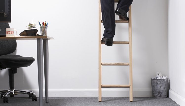 Man climbing ladder in office, low section